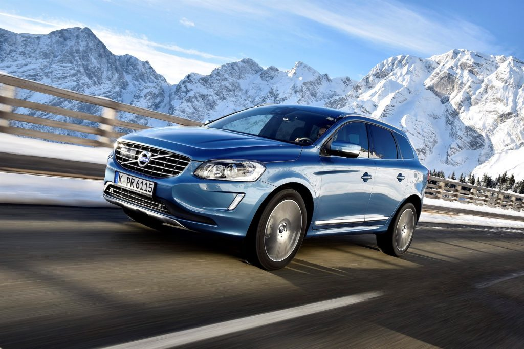 A 2017 Volvo XC60 T6 AWD luxury compact SUV travels on a highway past snow-capped mountains