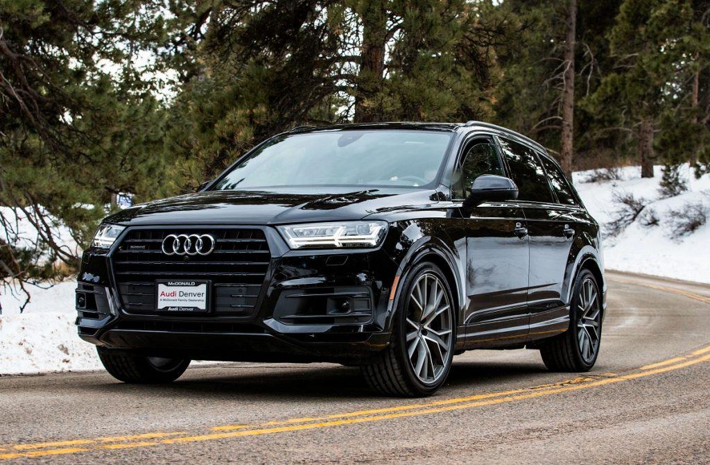 A black 2019 Audi Q7 driving down a snowy road.