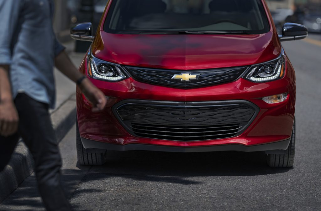 A red 2021 Chevy Bolt parked streetside shot from the front
