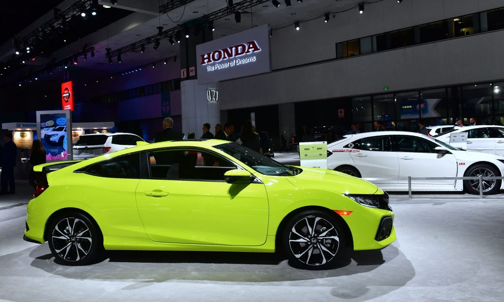 a yellow civic Si is on display at a car show
