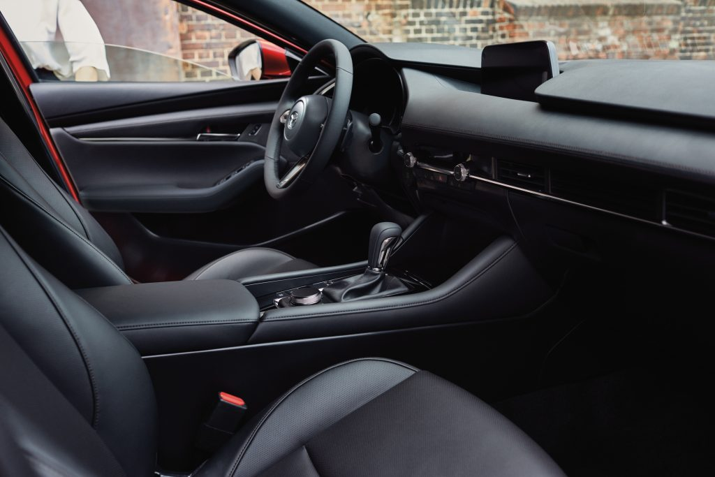 The interior of the 2021 Mazda 3 sedan, awash with chrome and leather
