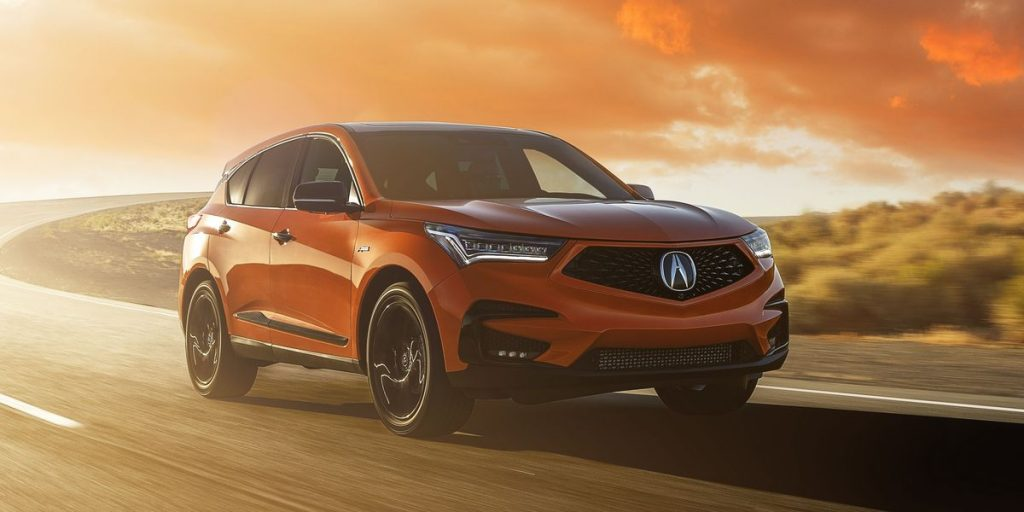 An orange 2021 Acura RDX driving down the road during a sunset