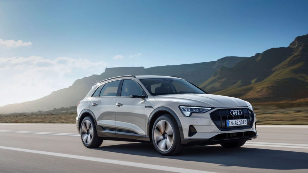 The 2021 Audi e-tron electric vehicle driving on an open country highway near grassy mountains