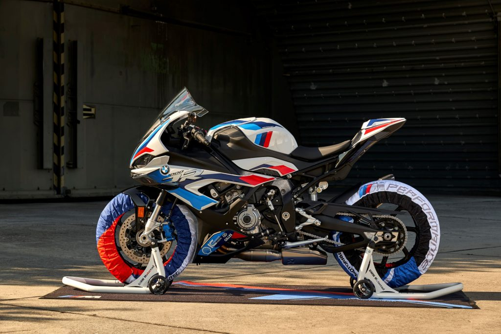 The side view of a white-blue-and-red 2021 BMW M 1000 RR on wheel stands with matching tire warmers