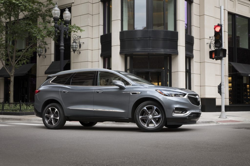 A dark-silver 2021 Buick Enclave midsize three-row SUV at a city intersection