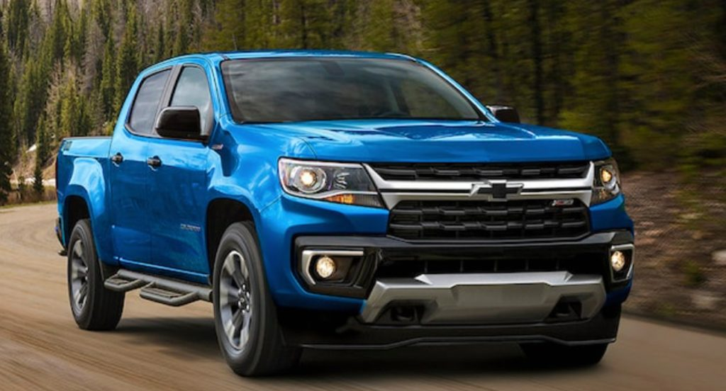 A blue 2021 Chevrolet Colorado is driving on the road.