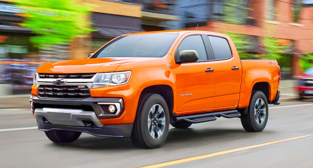 An orange 2021 Chevrolet Colorado pickup truck is driving on the road.