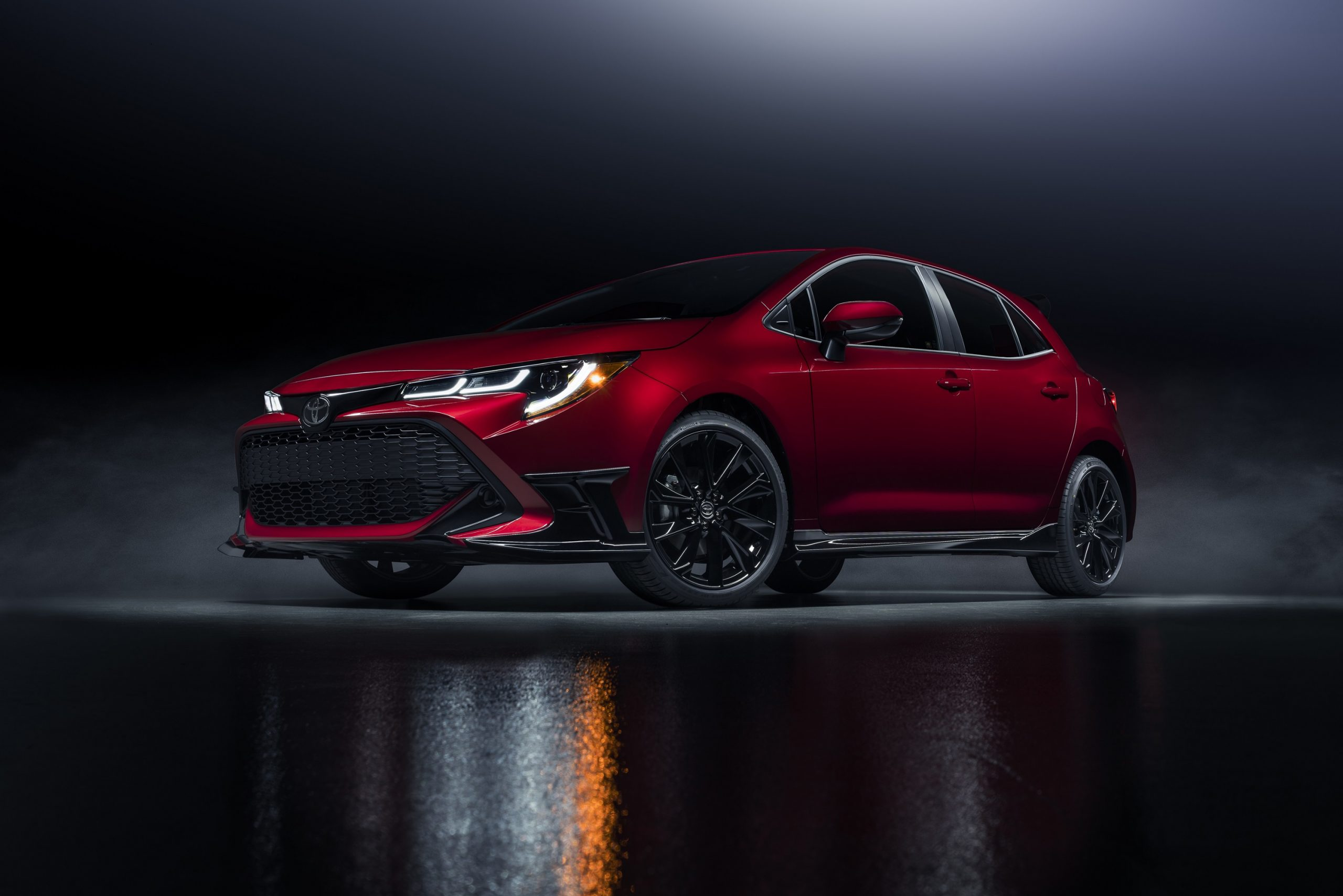 A red 2022 Toyota Corolla hatchback shot from the low front 3/4 in a studio