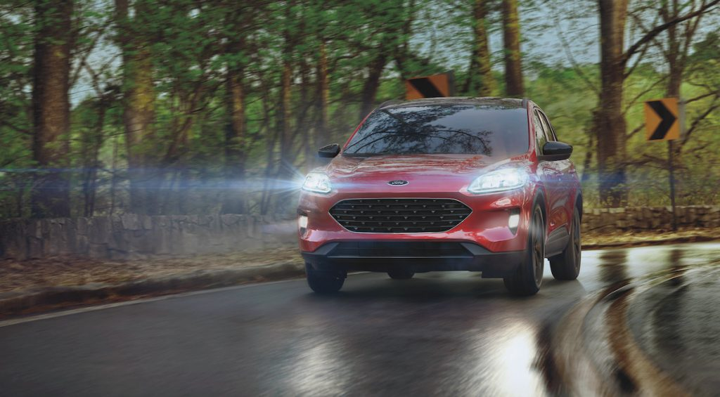A red 2021 Ford Escape compact SUV with its headlights illuminated travels on a wet road past trees on a rainy day