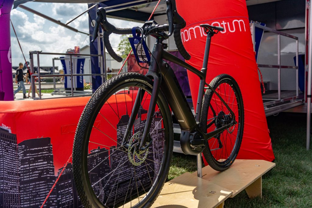 The front 3/4 view of a dark-purple 2021 Giant Revolt E+ Pro on a stand by a red tent