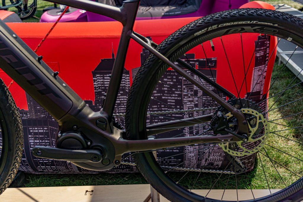 A close-up view of a dark-purple 2021 Giant Revolt E+ Pro's motor and rear derailleur