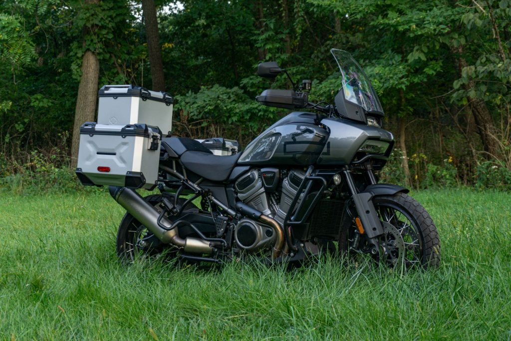A gray-and-black 2021 Harley-Davidson Pan America 1250 Special with accessories in a grassy field
