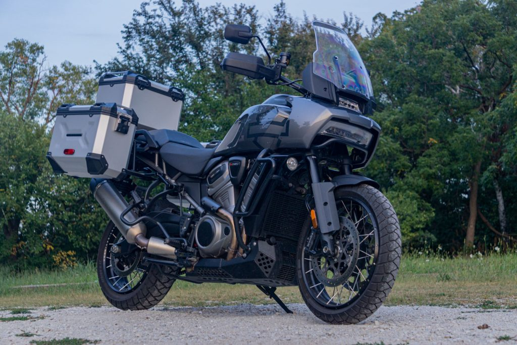 A low-angle view of a gray-and-black 2021 Harley-Davidson Pan America 1250 Special by a forest