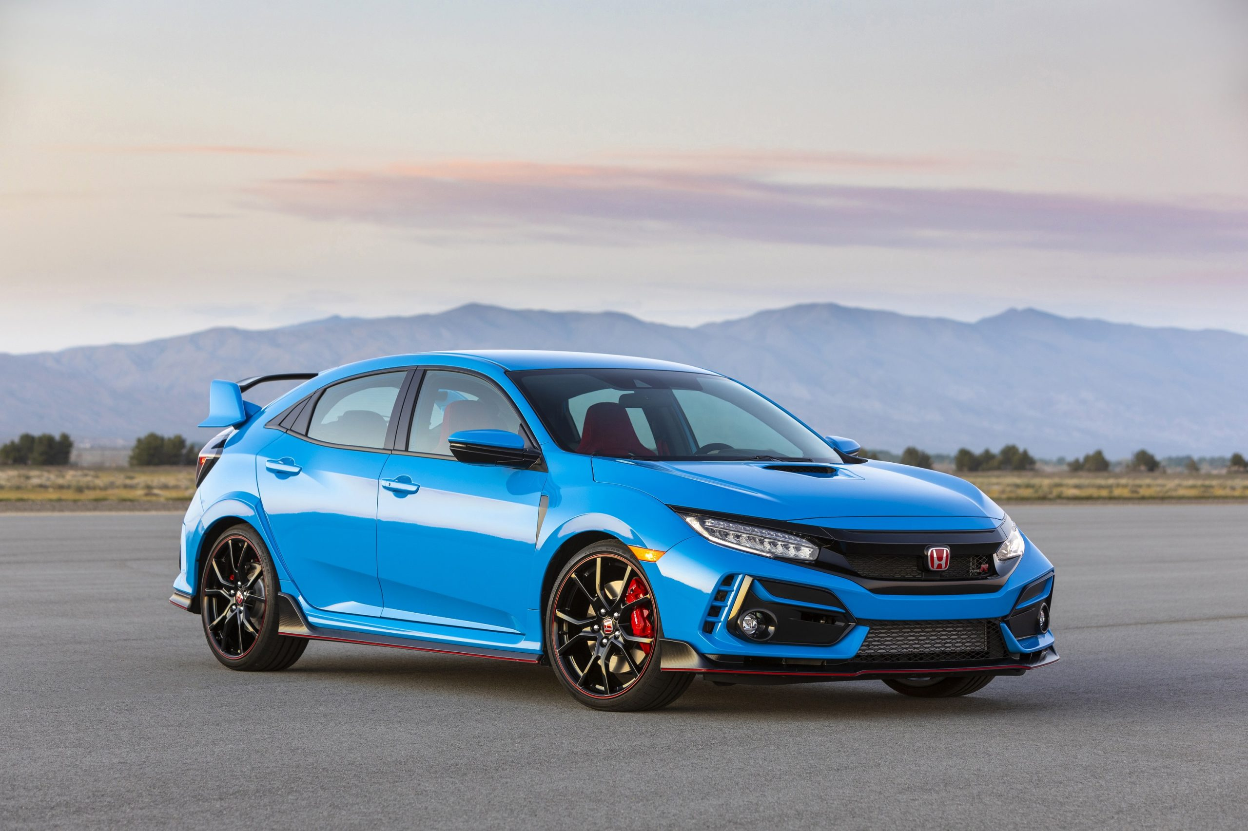 A blue Honda Civic Type R shot from the front 3/4 at sunset