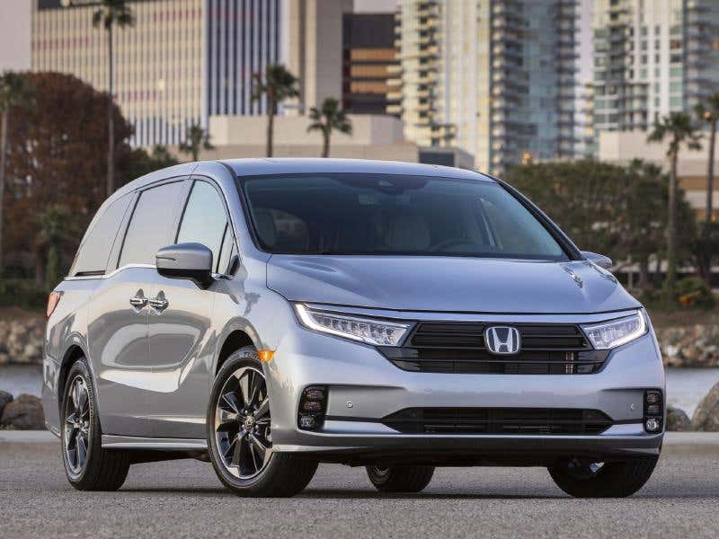 A silver 2021 Honda Odyssey parked outside with a city background