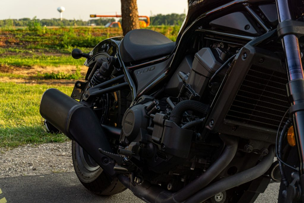 A closeup view of a black 2021 Honda Rebel 1100 DCT's engine, exhaust, seat, and rear suspension