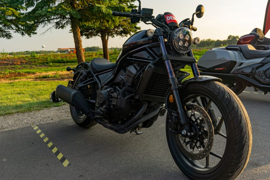 The front 3/4 view of a black 2021 Honda Rebel 1100 DCT in a parking lot