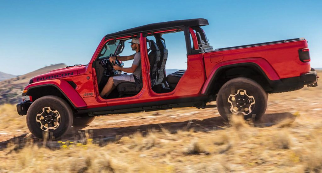 A red 2021 Jeep Gladiator with doors removed is seen off-roading.