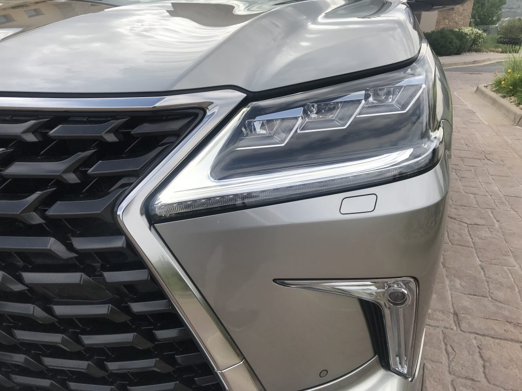 Headlight shot of the 2021 Lexus LX 570 as it sits in a parking lot driveway for our full review.