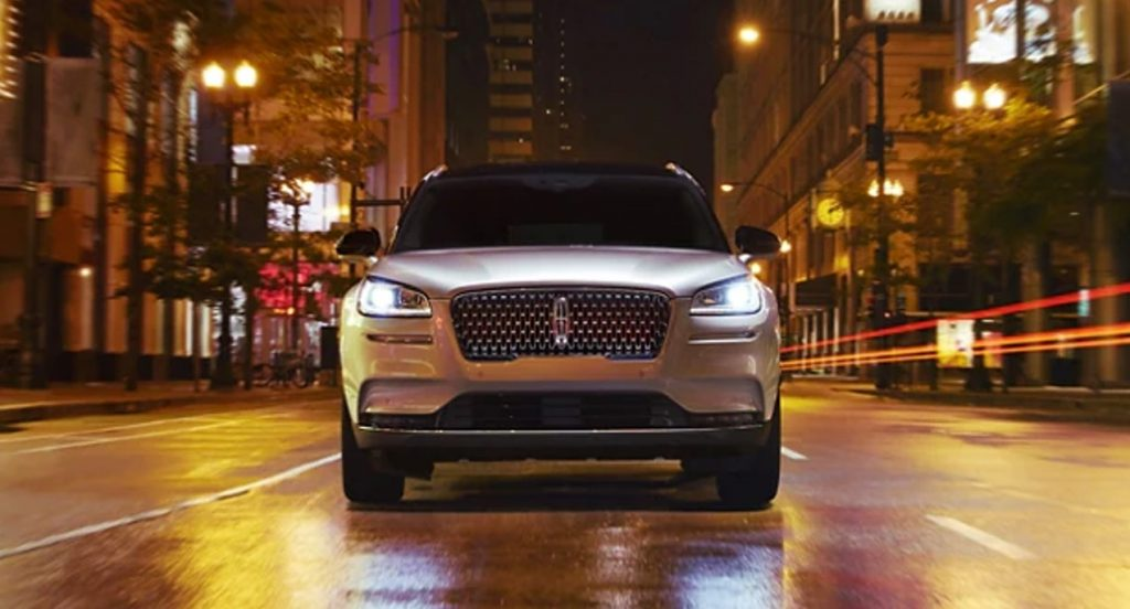 A silver 2021 Lincoln Corsair SUV is driving on the street.