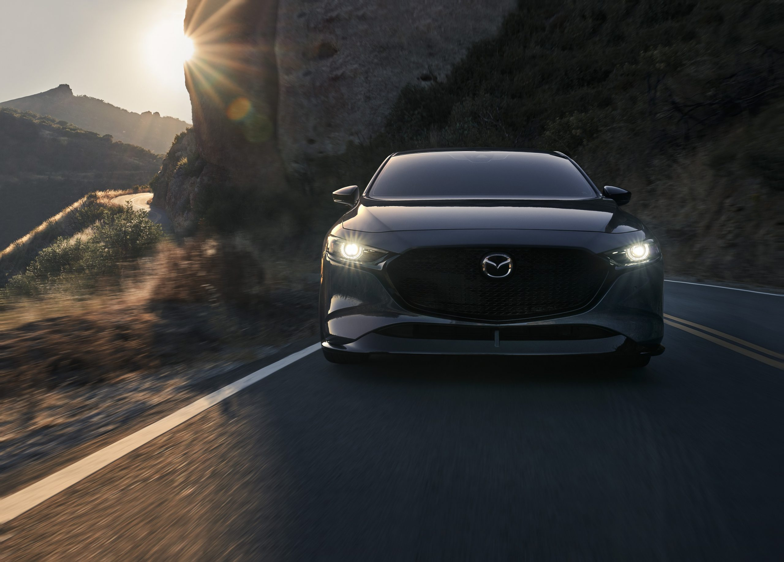 A grey Mazda 3 AWD hatchback shot from the front on a canyon road at sunset