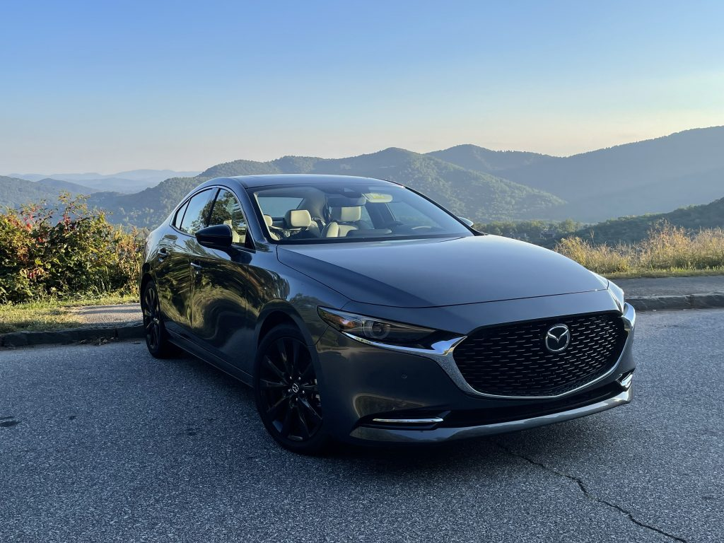The 2021 Mazda3 Turbo in front of a mountain view