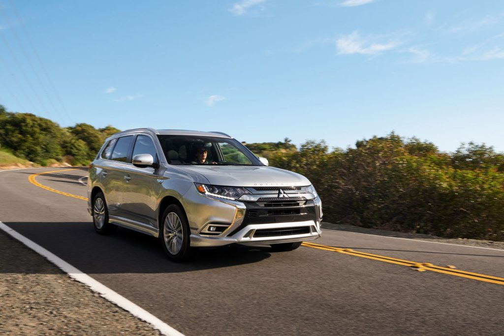 A 2021 Mitsubishi Outlander PHEV model in silver gray driving down a strip of highway