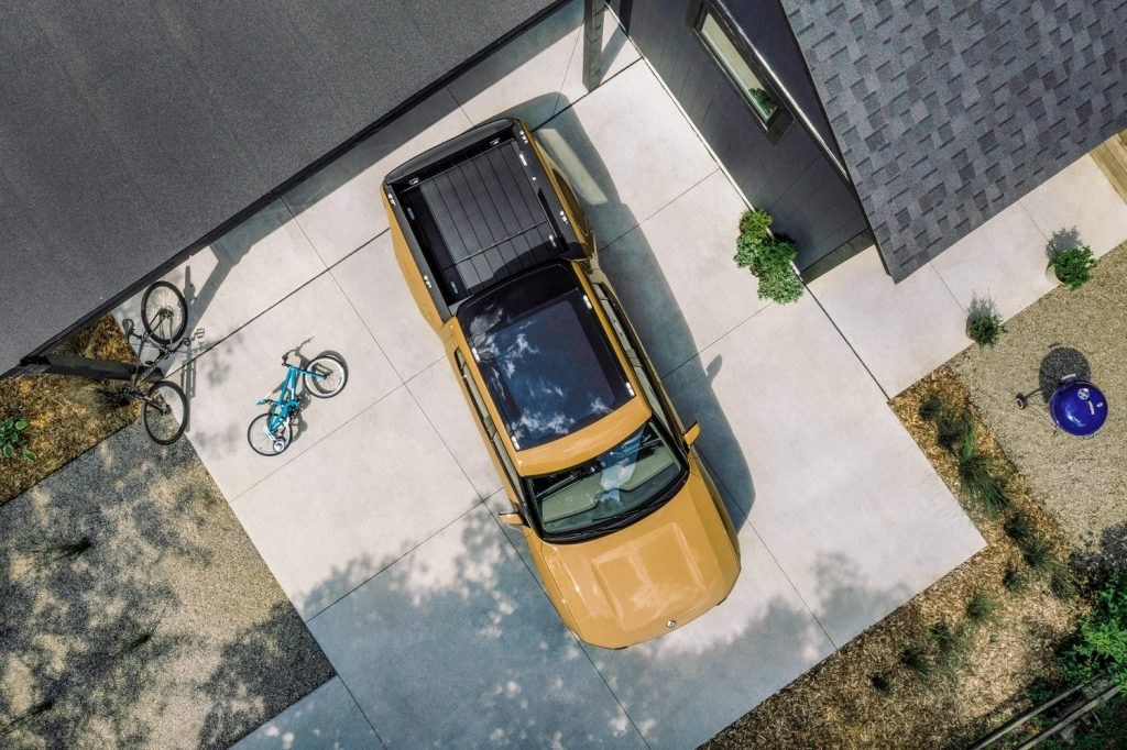 This is a yellow Rivian R1T electric truck. The Rivian is the first electric pickup to market. This Rivian promotional photo was taken by Andi Hendrick.