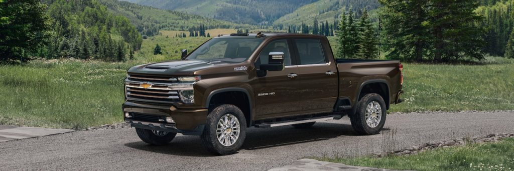 2021 chevrolet silverado high country in brown parked outside near a mountain and forest