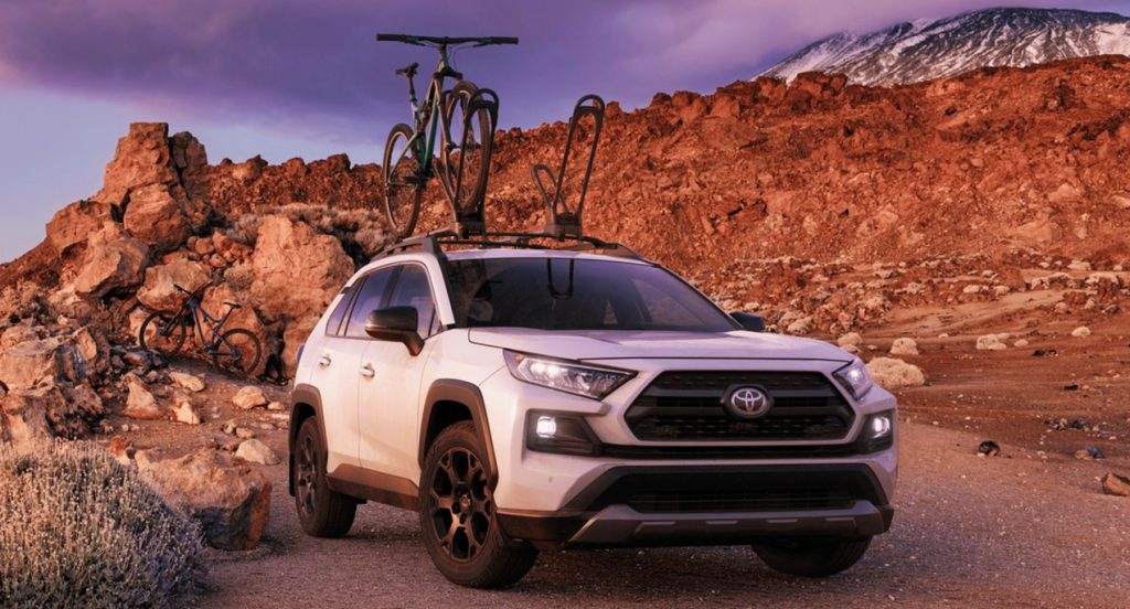 A white 2021 Toyota Rav4 TRD Off-Road is on a trail with mountains in the background. The SUV has a bike roof rack with a bike fastened to it.