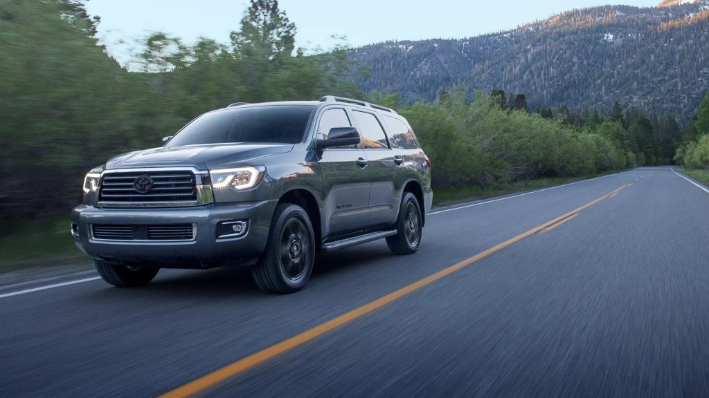 A 2021 Toyota Sequoia drives down an empty road at night.