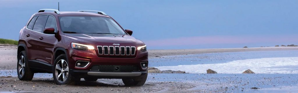 A red 2021 Jeep Cherokee parked on the beach.