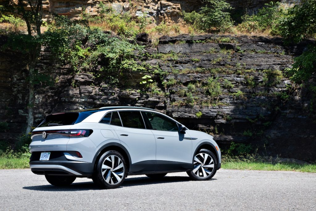 A light-gray 2021 Volkswagen ID.4 electric crossover SUV parked on a road next to a rocky cliff