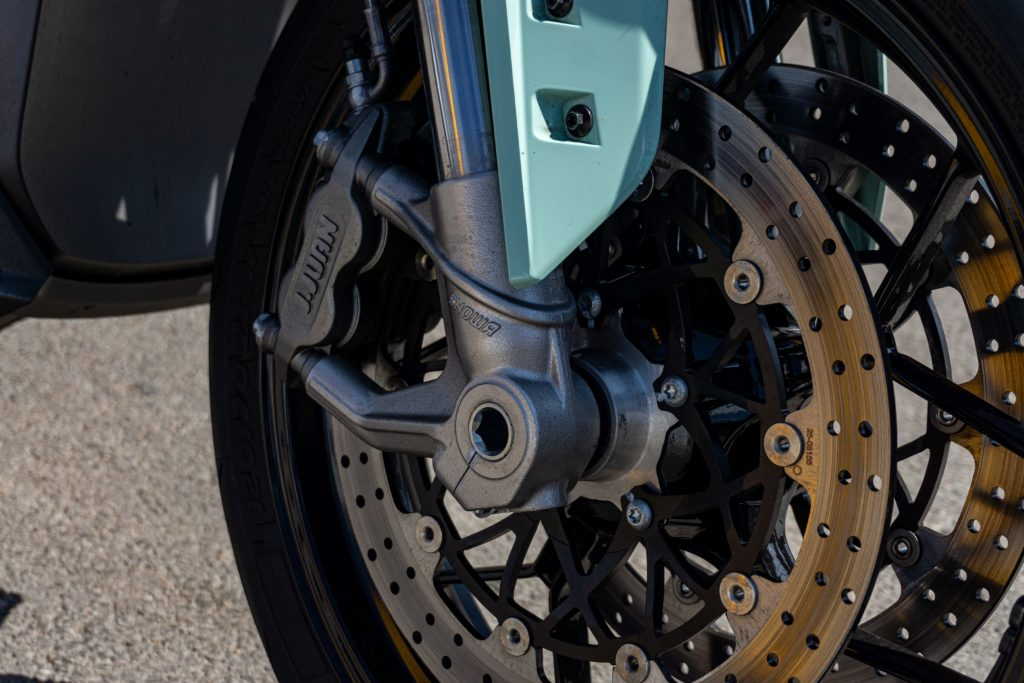 A close-up view of a mint-green 2021 Zero SR/F Premium's front brakes and the lower half of its fork