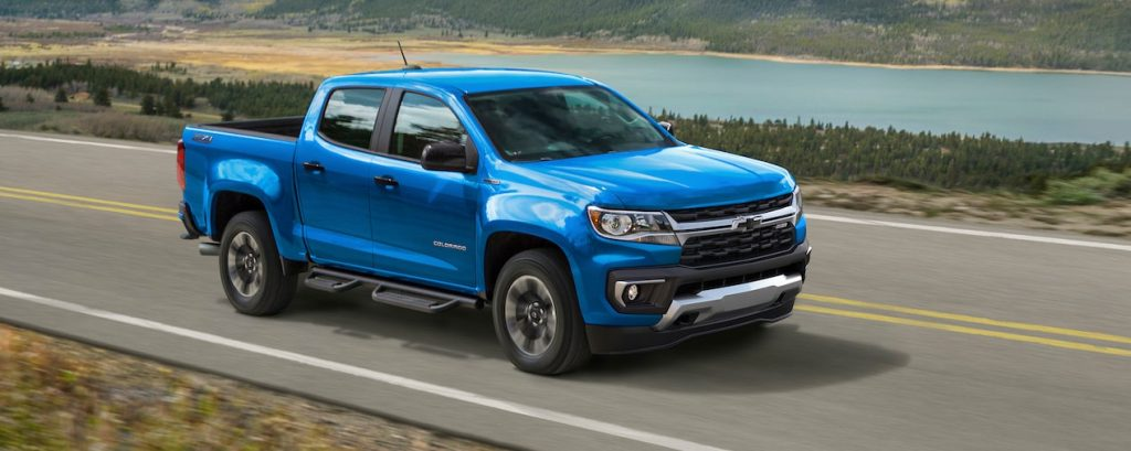 a bright blue 2021 Chevy Colorado driving at speed on a country highway