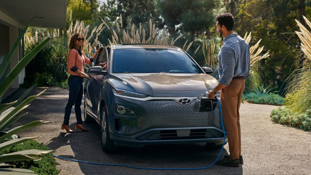 A taupe 2021 Hyundai Kona Electric being recharged by a couple.
