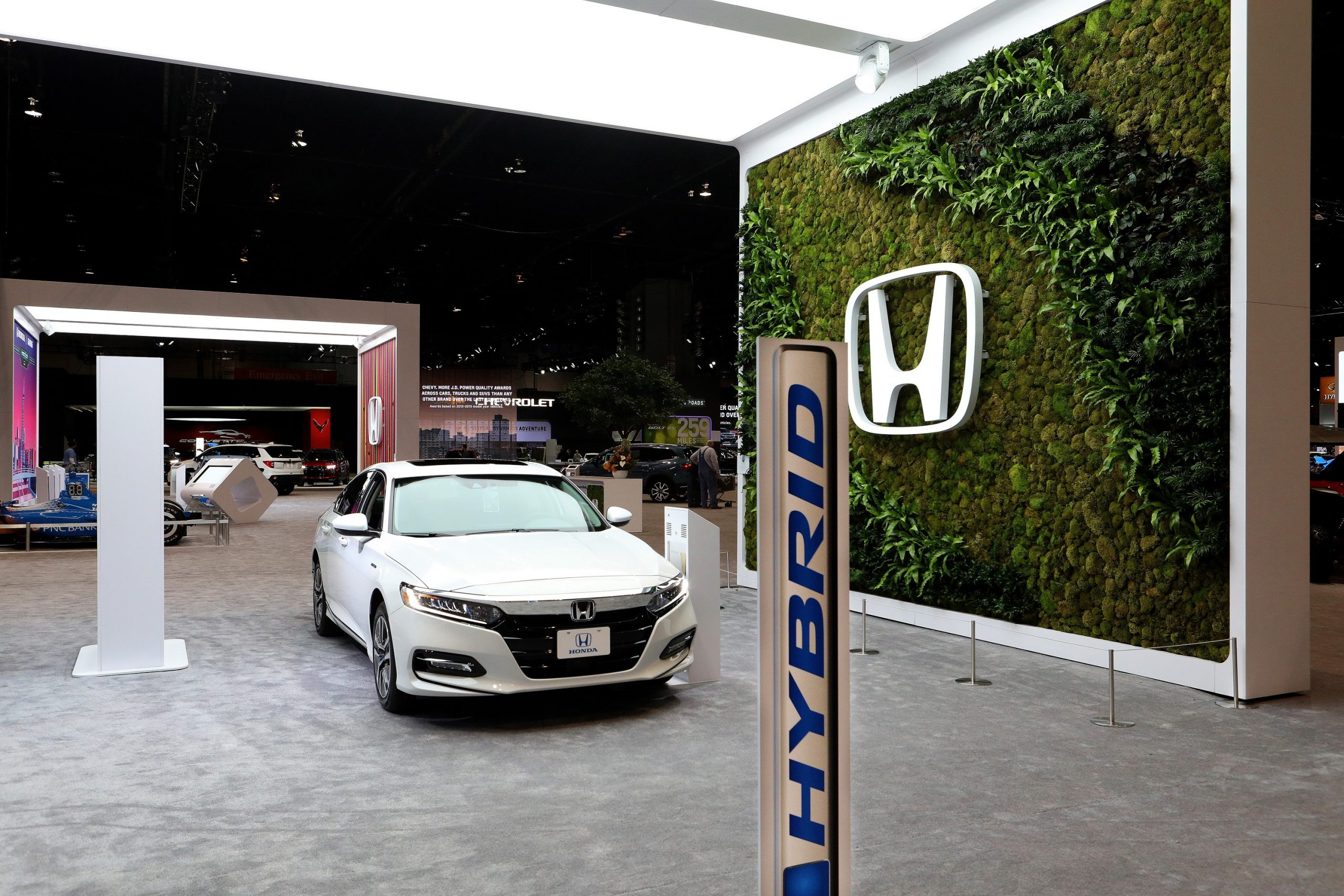 A white 2021 Honda Accord, one of the best midsized sedans on sale today, shot in an auto show booth from the front 3/4 angle