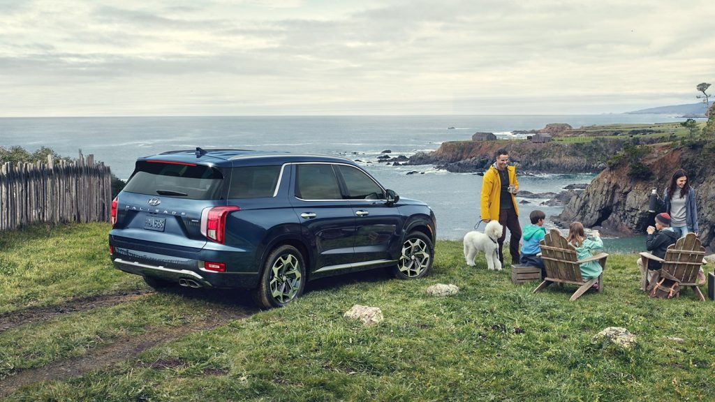 A navy blue 2021 Hyundai Palisade parked at the edge of a cliff iwth a family enjoying hot cocoa.