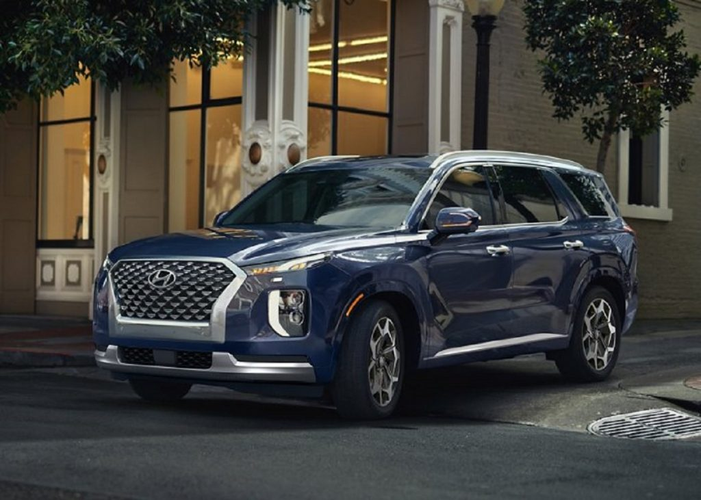A dark blue 2021 Hyundai Palisade pulling out of a side street.