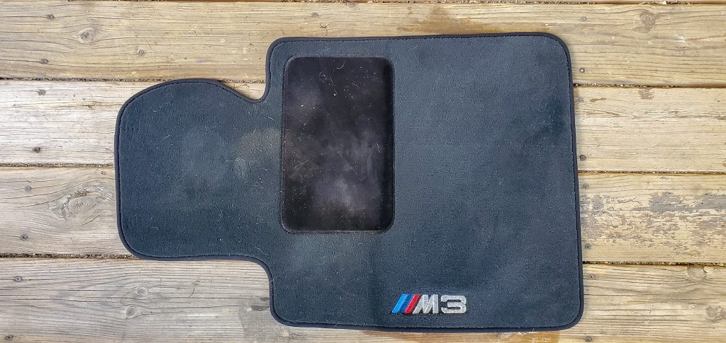 A dirty floormat, half treated with Meguiar's Carpet and Upholstery Cleaner, shows the cleaned side spot-free compared to the untreated side