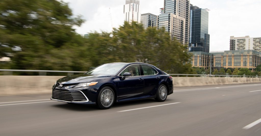 A new 2022 Toyota Camry rolls down a city highway with dark blue paint and a softer front end than last year's model