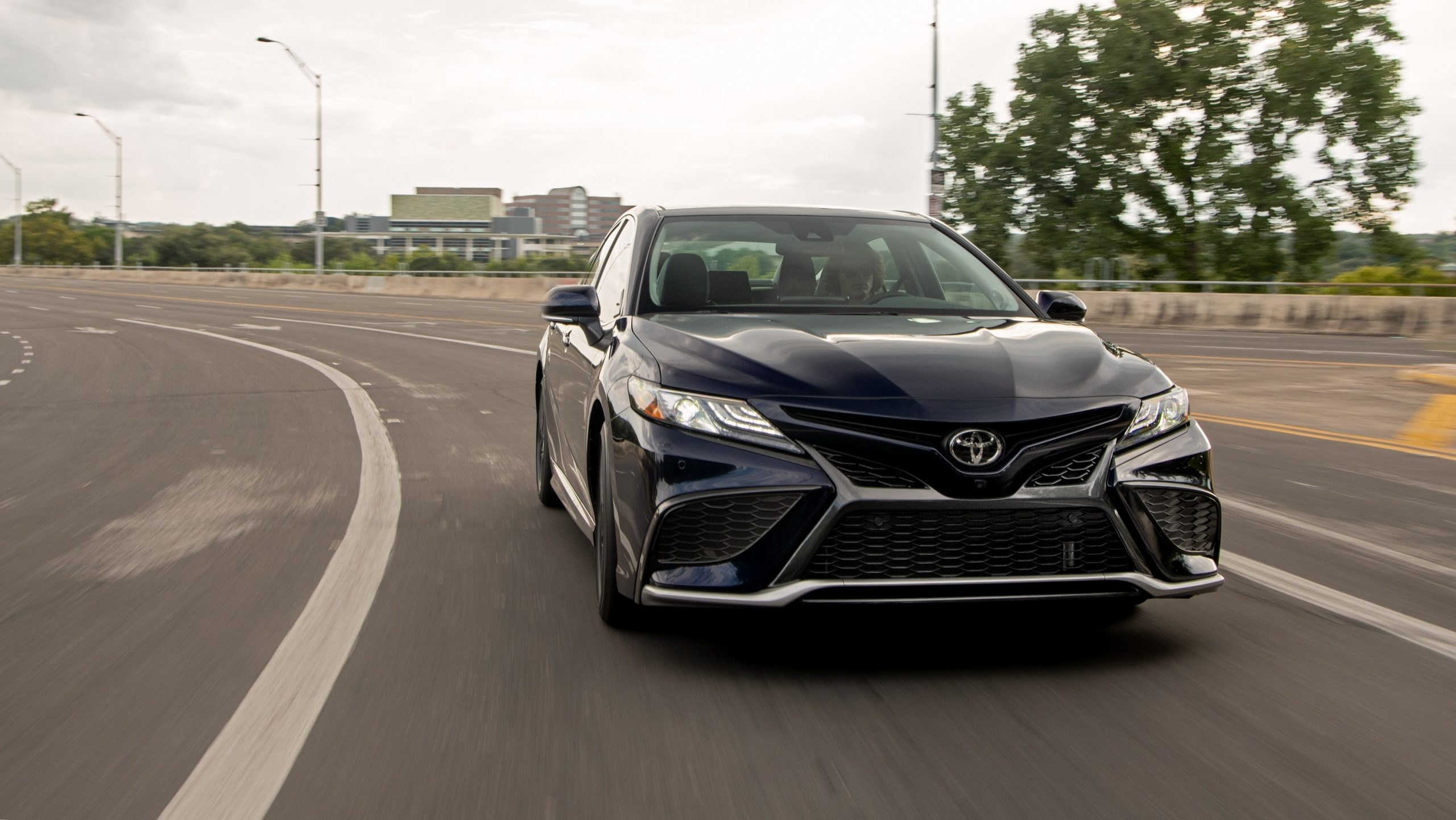 A blue 2022 Toyota Camry XLE shot from the front on a highway