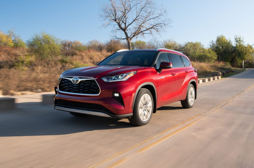 A red Toyota Highlander hybrid drives down a country road in the fall