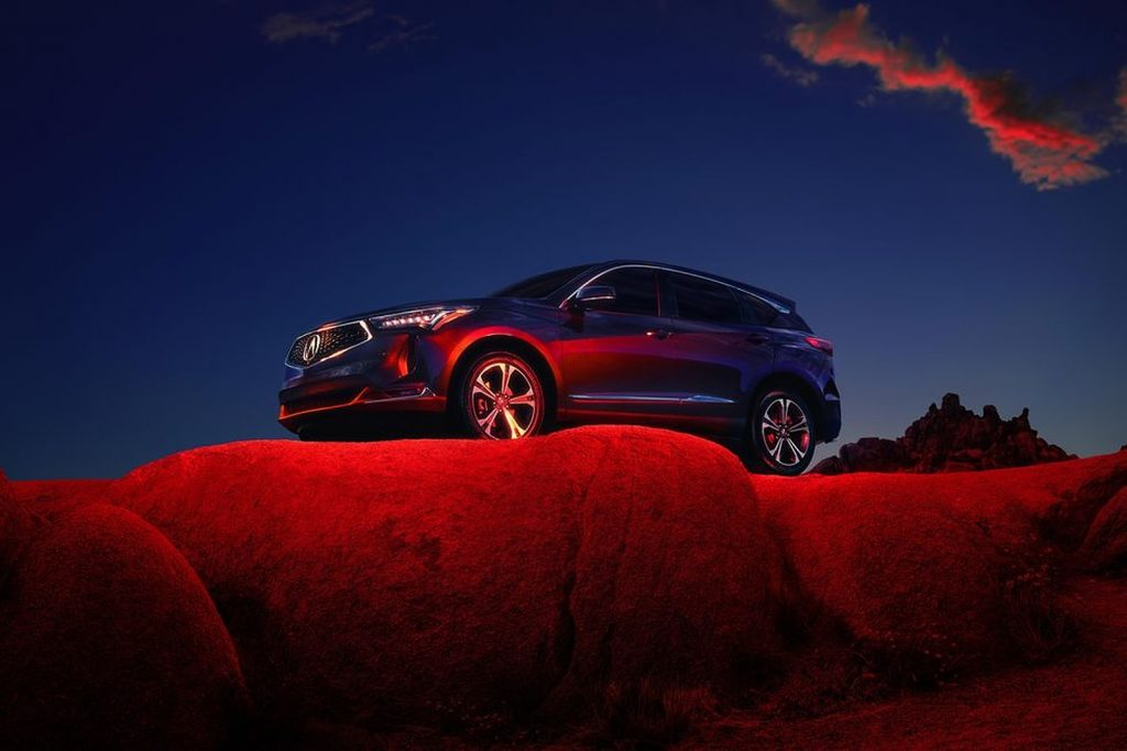 A blue 2022 Acura RDX parked outside on a cliff with red lighting