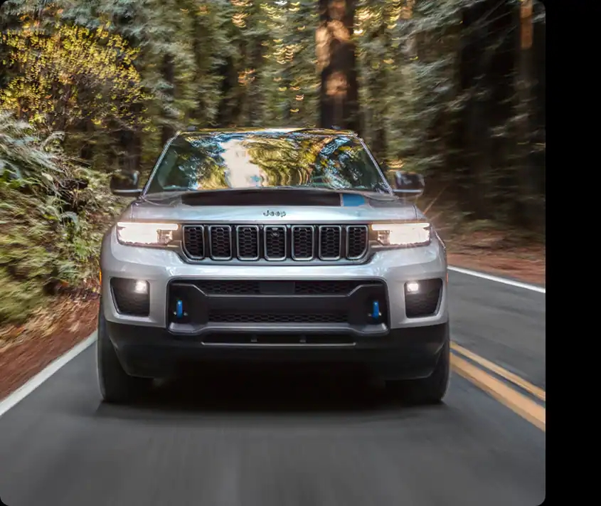 A silver 2022 Jeep Grand Cherokee driving down a wooded road.