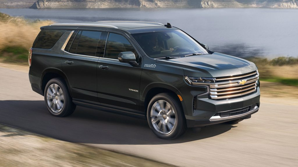 black 2022 Chevrolet Tahoe High Country driving near a lake