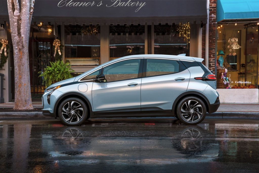 The 2022 Chevy Bolt parked on a wet downtown street
