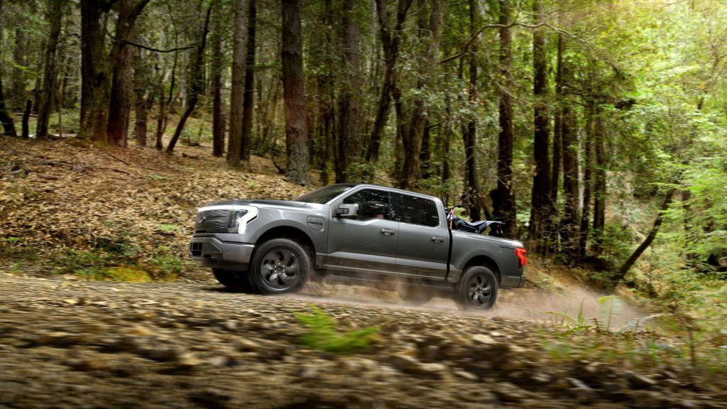 A grey 2022 Ford F-150 Lightning driving on a dirt road in a wooded area.