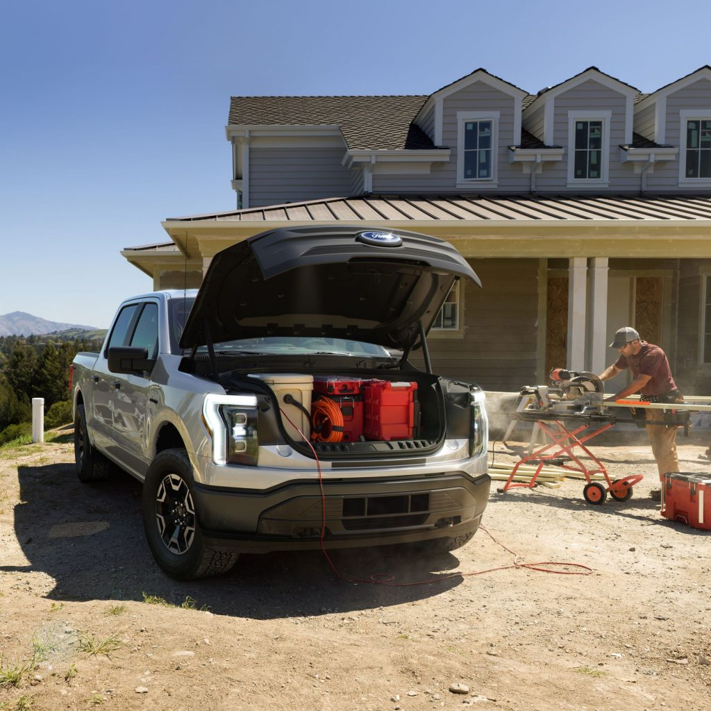 The front of a 2022 Ford F-150 Lightning with the frunk open at a construction site during a house build.