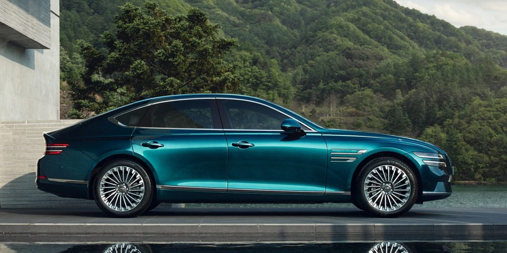 A blue 2022 Genesis Electrified G80 parked next to a tree-covered hill.